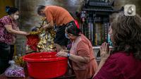 Seorang jemaat memperhatikan para jemaat lain yang sedang membersihkan patung di Vihara Amurva Bhumi, Jakarta, Kamis (4/2/2021). Ritual mencuci patung dewa serta bersih-bersih ini dilakukan dalam rangka menyambut perayaan Tahun Baru Imlek 2572. (Liputan6.com/Faizal Fanani)