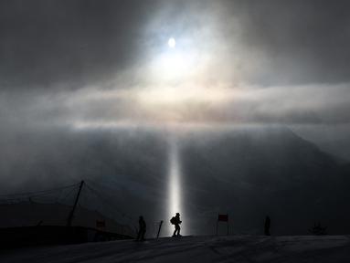 Pelatih berjalan melintasi sinar cahaya, saat melakukan pemeriksaan jalur ski dalam Kejuaraan FIS Alpine World Ski. (Foto: AFP/Fabrice Coffrini)