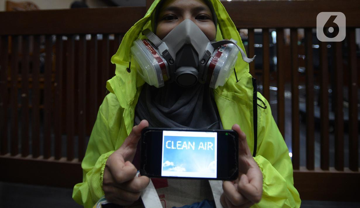 Aktivis yang tergabung dalam Koalisi Ibu Kota melakukan aksi sebelum sidang pembacaan putusan gugatan terkait polusi udara di Pengadilan Negeri Jakarta Pusat, Kamis (16/9/2021). Pada aksinya mereka menuntut pemerintah bisa mengendalikan polusi udara Jakarta dan sekitarnya. (merdeka.com/Imam Buhori)