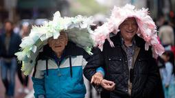 Peserta mengenakan topi hias dalam Parade Paskah tahunan dan Festival Bonnet di kota New York, AS, Minggu (21/4). Orang-orang turun ke jalan dengan kostum unik berpadu topi elegan yang pantas untuk menghadiri misa di Katedral St. Patrick dan gereja-gereja di dekatnya. (Johannes EISELE / AFP)