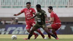Gelandang PS Tira Persikabo, Osas Saha, berebut bola pemain Persija Jakarta pada laga Shopee Liga 1 di Stadion Pakansari, Bogor, Selasa (16/7). Tira menang 5-3 atas Persija. (Bola.com/Yoppy Renato)