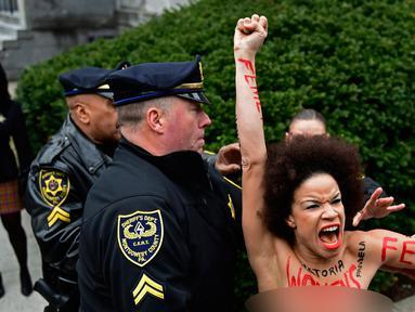 Pengunjuk rasa wanita mendatangi sidang kekerasan seksual komedian Bill Cosby di Gedung Pengadilan Montgomery, Pennsylvania, Amerika Serikat, Senin (9/4). Wanita itu ditahan karena tampil topless. (AP Photo/Corey Perrine)