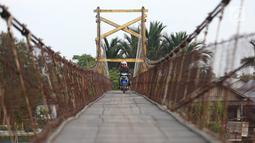 Warga melintasi jembatan penyeberangan di Sungai Martapura, Banjarmasin, Kalimantan Selatan, Selasa (27/3). Selain perahu, jembatan tersebut menjadi satu-satunya akses menyeberang bagi warga sekitar. (Liputan6.com/Immanuel Antonius)
