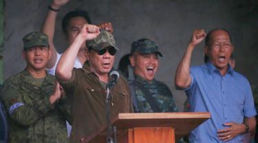 Presiden Filipina, Rodrigo Duterte bersorak saat mengumumkan pembebasan Kota Marawi di Filipina (17/10). Duterte mendeklarasikan Kota Marawi telah terbebas dari kelompok militan Maute yang berafiliasi dengan ISIS. (AP Photo/Bullit Marquez)