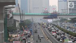 Kendaraan melintas berlatar pembangunan bentangan beton lintasan LRT di Jalan Gatot Subroto Jakarta, Kamis (7/11/2019). Saat ini pembangunan tiang pancang yang membentang di atas ruas jalan tol tersebut sudah tersambung. (Liputan6.com/Immanuel Antonius)
