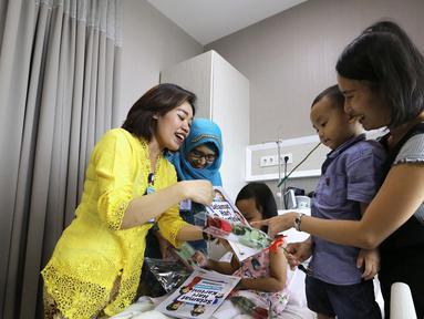 Karyawan dengan baju kebaya memberikan setangkai bunga dan buku kreativitas Kartini kepada pasien anak saat peringati Hari Kartini di RS Siloam TB Simatupang, Jakarta, Sabtu (21/4). (Liputan6.com/Fery Pradolo)