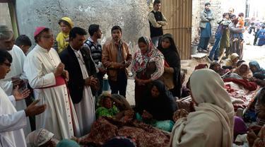 Sejumlah orang meratapi jenazah keluarganya di Toba Tek Singh, sekitar 338 km dari Islamabad, Selasa (27/12). Sedikitnya 24 orang di kalangan kelompok kecil Kristen di Pakistan tewas setelah mengonsumsi minuman keras oplosan saat perayaan Natal. (STR/AFP)