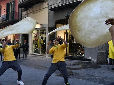 "Anggota Pizzaioli Acrobats Coldiretti  melakukan Pizzaioli atau seni memutar adonan piza di Naples, Italia, 7 Desember 2017. Seni memutar adonan piza milik masyarakat Napoli reSmi masuk dalam daftar ""warisan budaya tak benda"" UNESCO. (Tiziana FABI/AFP)"