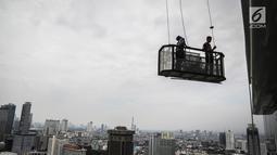 Pekerja naik gondola tanpa helm keselamatan beraktivitas di gedung bertingkat di Jakarta, Rabu (15/11). Banyak kejadian kecelakaan kerja di ketinggian disebabkan karena mahalnya peralatan pengaman pribadi yang ada di pasaran. (Liputan6.com/Faizal Fanani)
