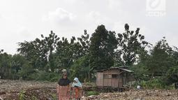 Dua wanita berjalan dekat tumpukan lumpur bercampur sampah dari proyek pengerukan situ Pedongkelan, Cimanggis, Depok, Rabu (28/11). Selain menimbulkan bau, banyaknya lumpur dan sampah membuat lingkungan warga tampak kumuh. (Liputan6.com/Herman Zakharia)