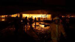 Petugas pemadam kebakaran mencoba memadamkan api di sebuah mal setelah gempa bumi melanda General Santos City, di pulau selatan Mindanao, Kamis (16/10/2019). Sejumlah bangunan dilaporkan roboh dan jaringan listrik putus usai gempa bermagnitudo 6,4 mengguncang Filipina selatan. (EDWIN ESPEJO / AFP)