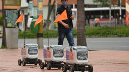 Robot pengiriman berjalan menyusuri jalan di Medellin, Kolombia, Selasa (21/4/2020). Robot yang bergerak dengan empat roda dengan bendera oranye di antena, membawa kiriman hingga berukuran 35 sentimeter persegi dan digunakan  mengantar pesanan restoran dengan pembayaran digital. (AP/Luis Benavides)