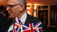 """Pendukung Brexit mengenakan topi Inggris di pesta Leave.EU setelah melihat hasil penghitungan sementara referendum Inggris yang menunjukkan mayoritas rakyat Inggris memilih """"Brexit"""" alias keluar dari Uni Eropa, di London, Kamis (23/6). (GEOFF CADDICK/AFP)"""