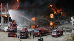 Petugas pemadam kebakaran berupaya memadamkan api yang membakar gudang-gudang di Pelabuhan Beirut, Lebanon, Kamis (10/9/2020). Beberapa pekerja mengatakan sedang ada pembersihan gudang di mana kebakaran tersebut terjadi. (AP Photo/Hassan Ammar)