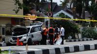 Kondisi mobil berwarna putih yang digunakan terduga teroris setelah serangan di luar markas polisi di Pekanbaru, Riau (16/5). Dalam serangan tersebut satu perwira tewas dan dua lainnya terluka. (AFP Photo/Dedy Sutisna)