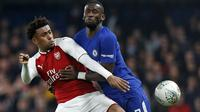 Duel pemain Arsenal, Alex Iwobi (kiri) dan pemain Chelsea, Antonio Rudiger ada laga leg pertama semifinal Piala Liga Inggris di Stamford Bridge, London, (10/01/2018). Chelsea bermain imbang 0-0 lawan Arsenal. (AFP/Ian Kington)