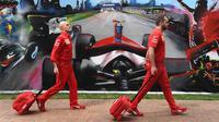 Anggota tim Ferrari tiba untuk mengepak peralatan mereka setelah Formula 1 Australia dibatalkan di Melbourne, Jumat (13/3/2020). F1 Australia batal digelar karena virus corona COVID-19. (William WEST/AFP)