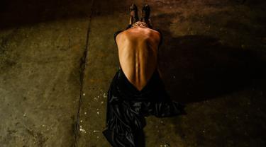 Seorang penari melakukan pemanasan di belakang panggun sebelum tampil dalam Turnamen Menari Tango di Festival Tango Internasional XIII di Medellin, Kolombia (18/6/2019). Festival Tango ini berlangsung dari 16 sampai 24 Juni 2019. (AFP Photo/Joaquin Sarmiento)