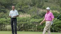 Presiden AS Barack Obama dan PM Malaysia, Najib Razak saat main golf di Hawaii, Rabu (24/12/2014). (AFP PHOTO/Nicholas KAMM)