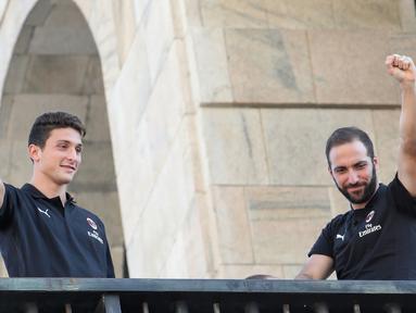 Pemain baru AC Milan, Gonzalo Higuain (kanan) dan Mattia Caldara menyapa suporter dari balkon di alun-alun pusat Milan Piazza Duomo (3/8). Higuain dan Caldara didapatkan Milan dari Juventus. (AFP Photo)