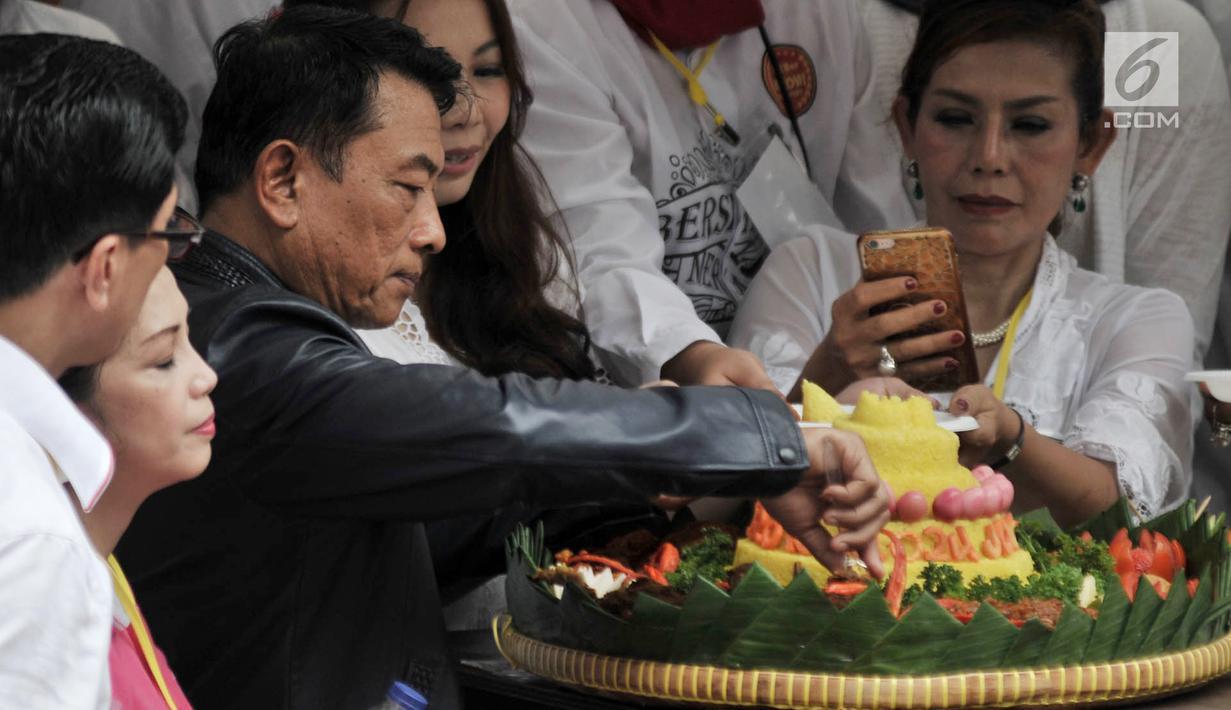Ketua Harian TKN Moeldoko memotong tumpeng saat syukuran relawan Jokowi-Ma'ruf Amin di Jakarta, Minggu (21/4). Acara syukuran tersebut diisi oleh doa bersama, mengheningkan cipta, dan potong tumpeng. (merdeka.com/Iqbal Nugroho)