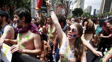 Ribuan mahasiswa bertelanjang dada menggelar aksi mogok nasional di Bogota, Kolombia, (17/3). Aksi tersebut merupakan protes terhadap sejumlah kebijakan pemerintah. (REUTERS/John Vizcaino)