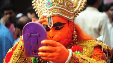 Seorang pemuja Hindu India berpakaian seperti dewa monyet Hanoman bersiap mengikuti festival Jayanti di Allahabad, India (18/10). Festival ini untuk memperingati kelahiran dewa Hindu Hanoman. (AFP Photo/Sanjay Kanojia)