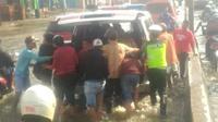 Pengantar jenasah dibantu Polisi mendorong mobil ambulans yang mogok saat melintasi rob di jalan Kaligawe Semarang. (foto:Liputan6.com/ist/edhie prayitno ige)