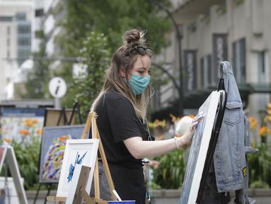 Seorang seniman mengerjakan karyanya dalam lomba lukis Art Masters di Vancouver, British Columbia, Kanada (22/7/2020). Sejumlah seniman ikut serta dalam lomba lukis yang digelar di Vancouver pada Rabu (22/7) tersebut. (Xinhua/Liang Sen)
