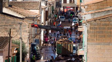 Sejumlah warga membersihkan rumah mereka yang terkena banjir bandang di Sant Llorenc, Mallorca, Spanyol (11/10). Banjir bandang tersebut telah menewaskan setidaknya 10 orang. (AP Photo/Francisco Ubilla)