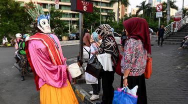 Foto pada 20 Maret 2019 menunjukkan ondel-ondel yang dioperasikan oleh seorang anak untuk mengamen di jalanan Jakarta. Seiring berjalan waktu, ondel-ondel yang dahulu sebagai ikon kesenian Betawi kini mudah ditemui di sejumlah jalan dan gang-gang di antara permukiman warga. (GOH CHAI HIN / AFP)