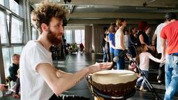 Imigran Suriah, Ali Hassan memainkan gendang saat mengajar tarian tradisional Arab Dabke di Berlin, Jerman, Minggu (15/4). (AP Photo/Jona Kallgren)