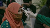 Tenaga kesehatan mengukur suhu tubuh tenaga pendidik sebelum vaksin COVID-19 di SMP 216, Jakarta Pusat, Selasa (6/4/2021). Menurut Menteri Kesehatan Budi Gunadi Sadikin, pemerintah akan memprioritaskan kelompok lansia dan juga tenaga pengajar dalam vaksinasi kali ini. (Liputan6.com/Faizal Fanani)