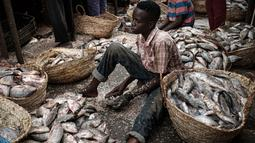 Pedagang ikan membuang sisik-sisik ikan di sebuah pasar ikan di dekat Sungai Nil, di kota kembar Khartoum, Omdurman (24/6/2019). Khartoum memiliki iklim tandus yang panas, hanya pada bulan Juli dan Agustus memiliki presipitasi yang signifikan. (AFP Photo/Yasuyoshi Chiba)