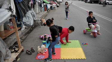 Anak-anak bermain di dekat tenda keluarga mereka yang didirikan di sebuah jalan di luar kamp pengungsi Eleonas di Athena (20/11/2019). Sekitar 14 pengungsi Afghanistan, termasuk keluarga dengan anak-anak, tinggal di luar kamp dalam tenda, tanpa fasilitas apa pun. (AFP/Louisa Gouliamaki)