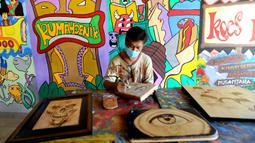 Arfan (55) menyelesaikan karya seni lukis bakar di galeri Rumah Oenik, Kampung Ragamukti, Tajur Halang, Bogor, Senin (28/9/2020). Arfan menjual karya seni lukis bakarnya dengan harga 300 ribu sampai jutaan rupiah dilihat dari besar dan tingkat kerumitannya. (merdeka.com/Arie Basuki)