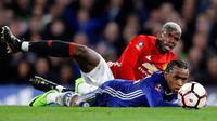 Pemain Manchester United, Paul Pogba dan pemain Chelsea, Willian, terjatuh saat berebut bola dalam perempat final Piala FA di Stadion Stamford Bridge, Senin (13/3). Chelsea lolos ke semifinal Piala FA setelah menang 1-0 atas MU. (AP Photo/Frank Augstein)