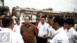 Menhub Budi Karya menggali keterangan dari petugas saat meninjau lokasi terbakarnya dua gerbong kereta Kerta Jaya kelas Ekonomi di dekat Stasiun Tanjung Priok, Jakarta, Kamis (25/8). (Liputan6.com/Faizal Fanani)