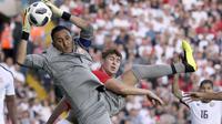 Kiper Kosta Rika, Keylor Navas mengamankan bola dari kejaran pemain Inggris, John Stones pada laga uji coba di Elland Road Stdium, Leeds, Inggris, (7/6/2018). Inggris menang 2-0.  (AP/Scott Heppell)