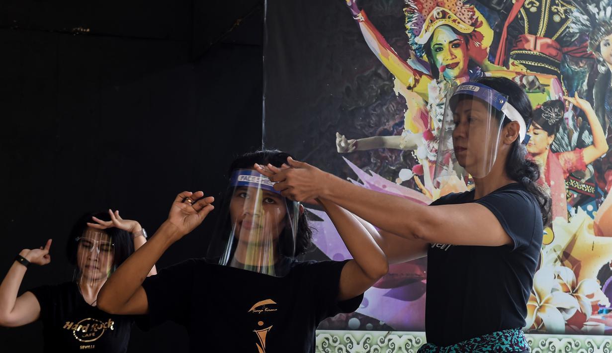 Anggota kelompok tari Surya Kirana mengenakan pelindung wajah mempraktikkan tarian tradisional Jawa klasik di Taman Mini Indonesia Indah (TMII), Jakarta, 11 Juli 2020. Mereka mengadakan latihan mingguan dengan mengikuti protokol kesehatan setelah TMII dibuka kembali. (Xinhua/Agung Kuncahya B.)
