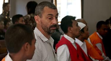 Warga negara Prancis, Samuel Pierre Danguny (kedua kiri) menunggu untuk menjalani sidang di Pengadilan Negeri Denpasar, Bali, Kamis (1/8/2019). Pierre diamankan pada 15 Maret 2019 dengan barang bukti berupa 6 paket ganja, 2 paket hasis, dan 1 paket sabu.  (SONNY TUMBELAKA/AFP)
