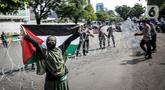 Seorang wanita mengibarkan bendera Palestina saat polisi memasang kawat berduri dalam aksi solidaritas untuk rakyat Palestina di Depan Kedutaan Besar Amerika Serikat, Jakarta (18/5/2021). Massa mengutuk dan mengecam keras kekerasan yang dilakukan Israel atas Palestina. (Liputan6.com/Faizal Fanani)