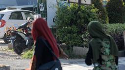 Dua wanita muslim berjalan melewati papan izin mendirikan bangunan (biru) di bekas lokasi bom Bali Sari Club di Kuta, Bali, Jumat (26/4). Perdana Menteri Australia Scott Morrison memprotes rencana pembangunan restoran di lahan bekas Sari Club yang merupakan lokasi pemboman Bali (SONNY TUMBELAKA/AFP)