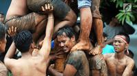 Para peserta berupaya mangambil hadiah, pada lomba panjat pinang di Perumahan Griya Pamulang 2, Tangerang Selatan, Jumat (17/8). Lomba yang diselengarakan oleh Bina Remaja ini dalam rangka memeriahkan HUT Ke-73 RI. (Merdeka.com/Dwi narwoko)