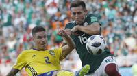 Pemain Swedia, Mikael Lustig (kiri) menghalau bola dari kejaran pemain Meksiko, Hector Herrera pada laga grup F Piala Dunia 2018 di Yekaterinburg Arena, Yekaterinburg, Rusia, (27/6/2018).  Swedia menang telak 3-0 atas Meksiko. (AP/Eduardo Verdugo)