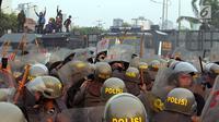 Polisi menghalau mahasiswa dalam demonstrasi menolak pengesahan RUU KUHP dan revisi UU KPK di depan Gedung DPR, Jakarta, Selasa (24/9/2019). Polisi menghalau mahasiswa yang berusaha masuk ke area Gedung DPR. (Liputan6.com/JohanTallo)