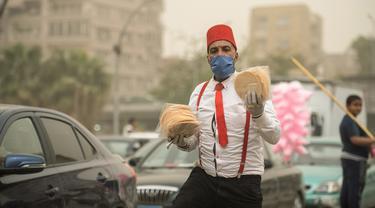 Seorang pedagang asongan yang mengenakan masker terlihat di sebuah jalan di Kairo, Mesir, pada 5 April 2020. Mesir pada Sabtu (4/4) melaporkan lima kematian baru akibat infeksi COVID-19, menjadikan total kasus kematian di negara tersebut mencapai 71. (Xinhua/Wu Huiwo)