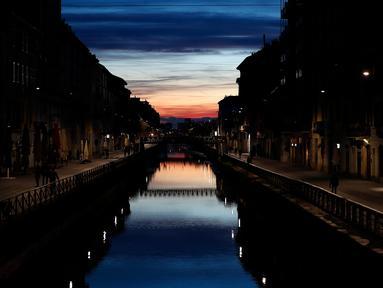 Beberapa orang berjalan di Kanal Naviglio Grande, Milan, Italia, Selasa (10/3/2020). Tak seperti biasanya yang selalu ramai, merebaknya virus corona (COVID-19) membuat salah satu tempat favorit bagi kehidupan malam di Milan tersebut kini terlihat sepi. (AP Photo/Antonio Calanni)