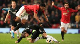 Striker Manchester United, Anthony Martial, dijatuhkan gelandang AZ Alkmaar, Teun Koopmeiners, pada laga Liga Europa di Stadion Old Trafford, Manchester, Rabu (12/12). MU menang 4-0 atas AZ. (AFP/Lindsey Parnaby)