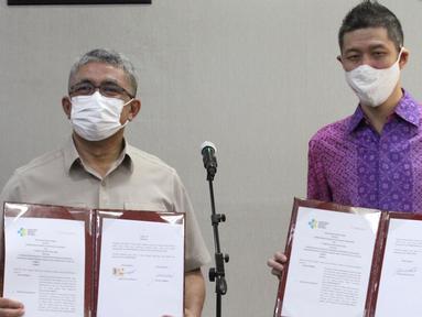Sekretaris Jenderal Kemenkes Oscar Primadi dan CEO & Cofounder Halodoc Jonathan Sudharta menunjukkan penandatanganan nota kesepahaman (MoU) di Gedung Kemenkes, Jakarta Senin (1/3/2021). Kerjasama dalam rangka percepatan program vaksinasi Covid-19. (Liputan6.com/Fery Pradolo)